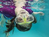 foto of upside  - little girl having fun and swimming upside down underwater - JPG