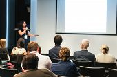 stock photo of public speaking  - business conference. people sitting rear and woman speaking at the screen