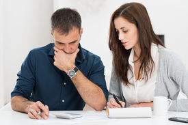 foto of budget  - Portrait Of A Worried Couple Calculating Financial Budget - JPG