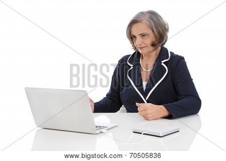 Portrait: Competent Senior Businesswoman Sitting At Desk With Computer.
