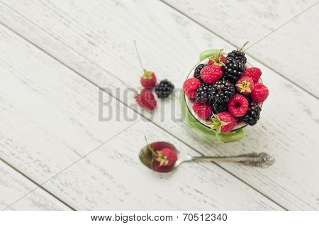 Pottery jar with raspberries and blackberries on a wooden backgroun.
