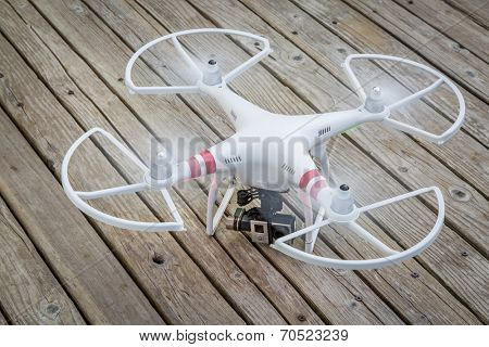 FORT COLLINS, CO, USA - AUGUST 4, 2014:  Radio controlled DJI Phantom quadcopter drone with GoPro Hero video camera taking off from a wooden deck