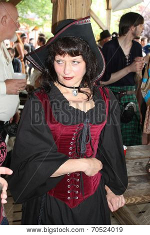 MUSKOGEE, OK - MAY 24: Woman dressed in historical costume walks around the village at the Oklahoma 19th annual Renaissance Festival on May 24, 2014 at the Castle of Muskogee in Muskogee, OK.