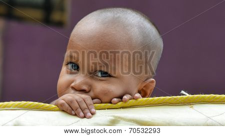 one poor little child looking at camera behind broken mattress
