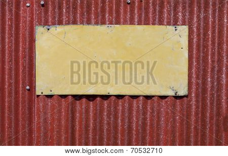 Empty Old painted metal plate tag screwed on red wall