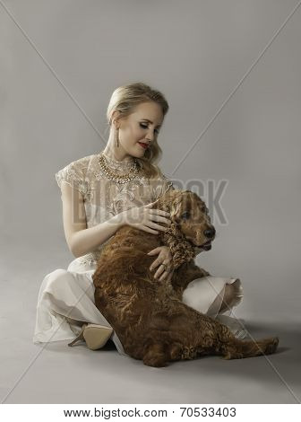 Blonde woman playing with dog on her lap