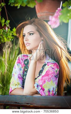 Beautiful female portrait with long red hair outdoor. Genuine natural redhead with colored blouse
