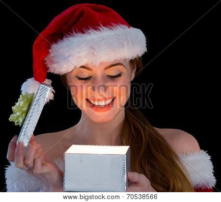 Pretty redhead in santa outfit opening a gift on black background