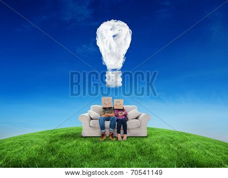 Silly employees with arms folded wearing boxes on their heads against cloud light bulb