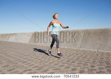 Active senior woman jogging on the pier on a sunny day