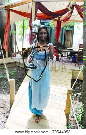 MUSKOGEE, OK - MAY 24: Woman offers a hookah for visitors at the Oklahoma 19th annual Renaissance Festival on May 24, 2014 at the Castle of Muskogee in Muskogee, OK.