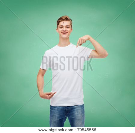 gesture, advertising, education, school and people concept - smiling young man in blank white t-shirt pointing fingers on himself over green board background