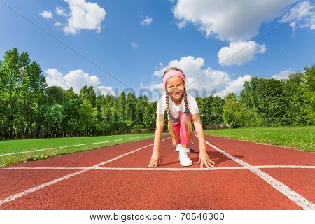 Girl in ready position on bend knee to run