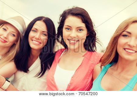 summer holidays and vacation concept - group of smiling girls chilling on the beach