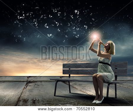 Young woman sitting on bench and playing fife