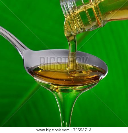 honey drops from a spoon on natural green background
