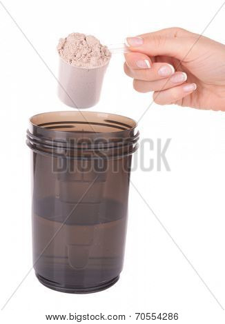 Female hand holding scoop with whey protein powder and plastic shaker isolated on white