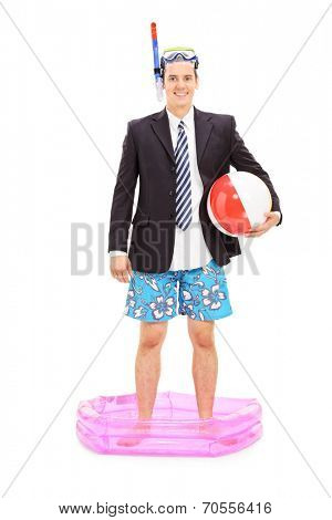 Full length portrait of a businessman with snorkel standing in a small pool isolated on white background