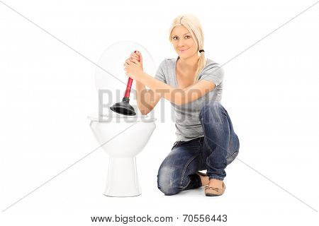 Young woman holding a plunger seated by a toilet isolated on white background