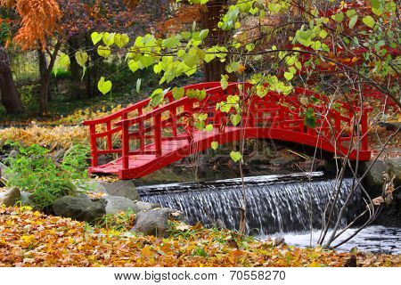 Red bridge and water falls in Japanese garden