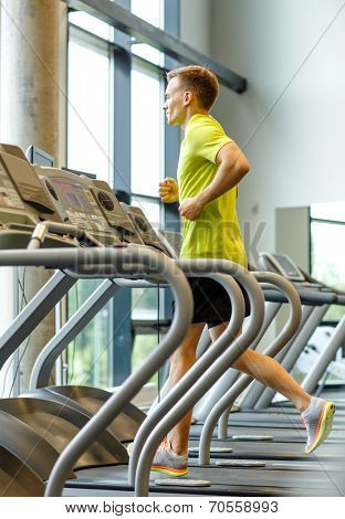 sport, fitness, lifestyle, technology and people concept - smiling man exercising on treadmill in gym