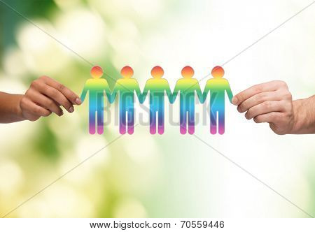 community, unity and teamwork concept - close up of multiracial couple hands holding paper chain gay people cutout over green background