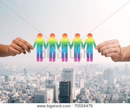community, unity and teamwork concept - close up of multiracial couple hands holding paper chain gay people cutout over city background