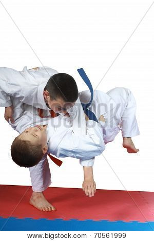 On the mat sportsmen are training judo throws