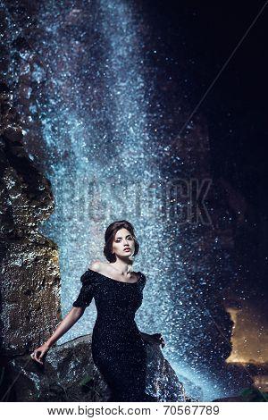 Woman posing near waterfall.