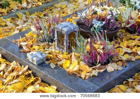 Autumn Decoration On The Tomb Full Of Leaves.