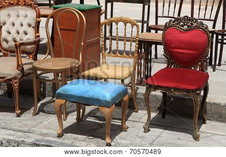 Collection Of Old Broken Chairs On The Flea Market.