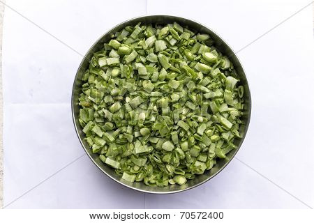 Finely chopped broad beans kept in a vessel read to be cooked