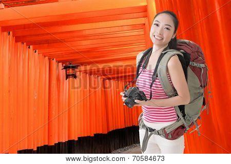 Happy smiling Asian young female backpacker with camera in Fushimi Inari Taisha, Japan.