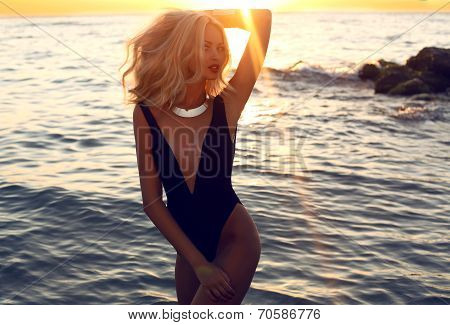 Sexy Woman With Blond Hair In Swimsuit Posing On Sunset