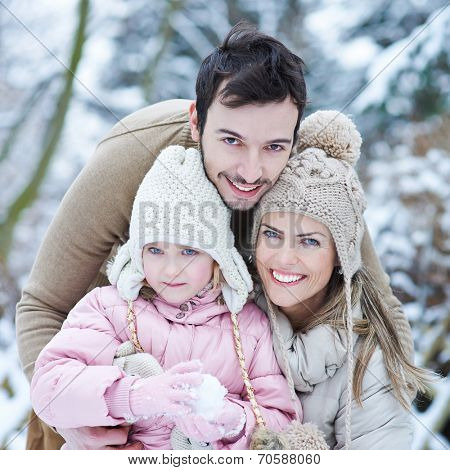 Happy family with child smiling outdoors in winter snow