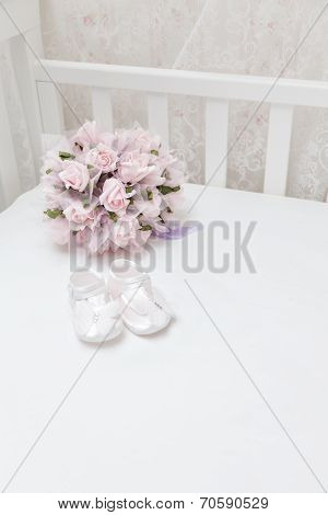 Pink Flowers And Children's Sandals On The White Bed