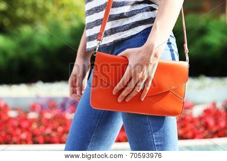 Girl with bag over his shoulder outdoors