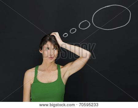 Beautiful young student thinking with a thought balloon on a chalkboard