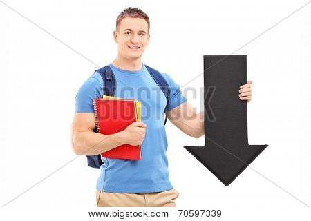 Male student holding a big black arrow pointing down isolated on white background