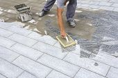 pic of grout  - Worker grouting tiles with rubber trowel and gray cement mortar - JPG