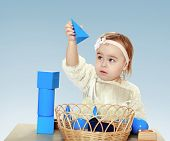 picture of montessori school  - little girl sitting at the table playing with cubes and pyramids on a blue background in the Montessori classroom - JPG