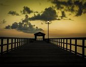 pic of gulf mexico  - The sunrise reflects yellow skies over an empty pier on the Gulf of Mexico - JPG