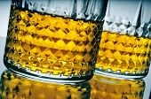 picture of bing  - closeup of some lowball glasses with whisky on a reflecting surface - JPG