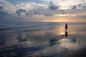 stock photo of deserted island  - A person walking along a deserted beach at sunset carrying an underwater camera and short flippers - JPG