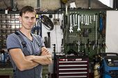 foto of grease  - Friendly garage worker or mechanic standing in front of his tools in a garage - JPG
