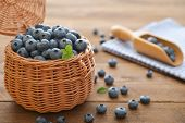 foto of wooden basket  - Fresh blueberry in wicker basket on wooden background - JPG