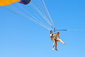 stock photo of parasailing  - man and girl parasailing on parachute in blue sky in summer day - JPG