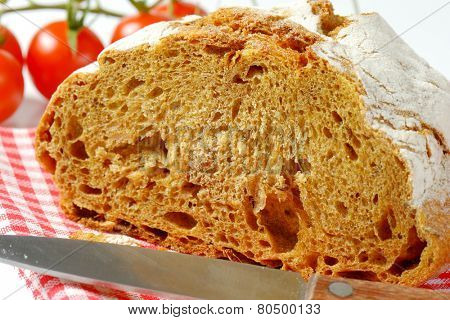 detail of sliced bread and kitchen knife on checkered dishtowel