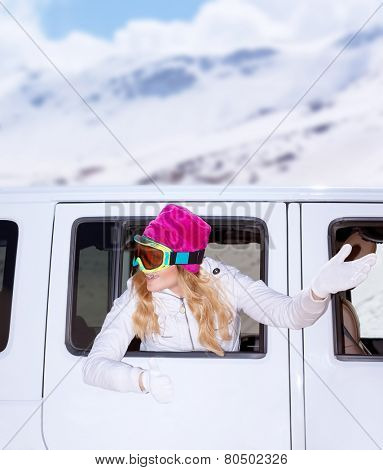 Cheerful female looks out from the car window and waved hand to next auto, wearing goggles, going to luxury ski resort, enjoying winter holidays