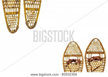 two pairs of vintage wooden snowshoes with leather binding isolated on white with a copy space